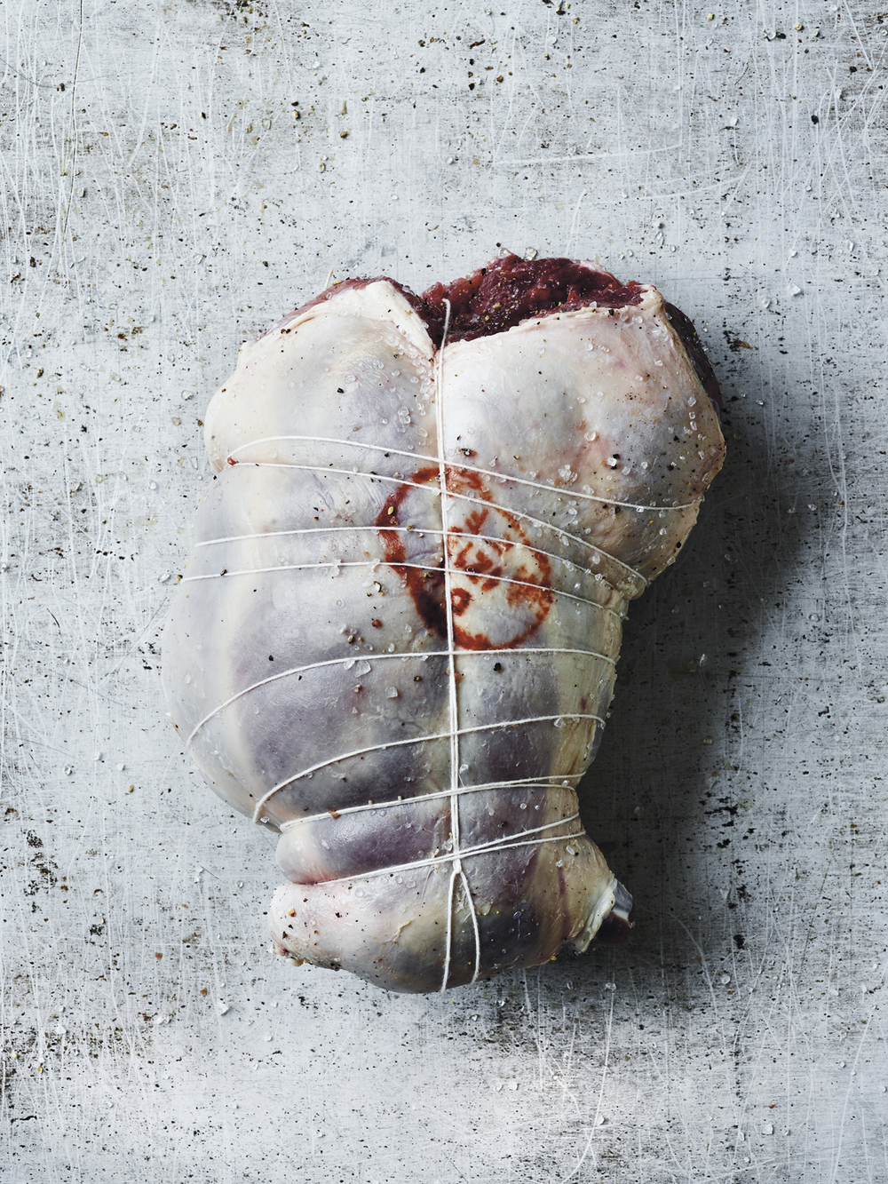 7. Når du kommer til enden, lukker du steika ved å trekke hyssingen gjennom den løkka du startet med, og drar til. Forvarm ovnen til 250 grader. Senk varmen til 65C° og stek lammet i cirka 45 minutter per kilo.Kjernetemperaturen skal være 65C° når du serverer det.Husk at temperaturen stiger noen grader mens kjøttet hviler før utskjæring.