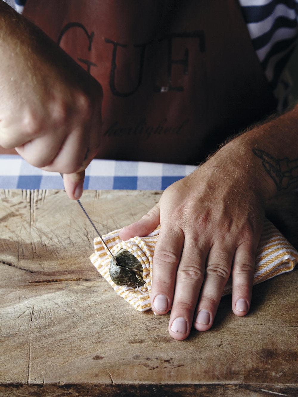 2.  Stikk østerskniven (liten, skarp sak) inn på baksiden av østersen, ved siden av festet, og vrikk fra side til side samtidig med at du presser inn. Gjør dette til du hører et slags klikk.