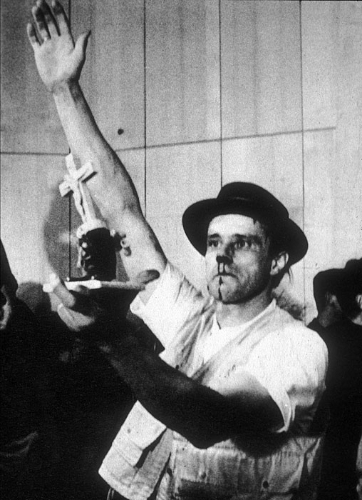 Photograph from a performance at the Technical College Aachen, in 1964.  The performance was part of a festival of new art coinciding with the 20th anniversary of an assassination attempt on Adolf Hitler.  The performance was interrupted by a group of students, one of whom attacked Beuys, punching him in the face.