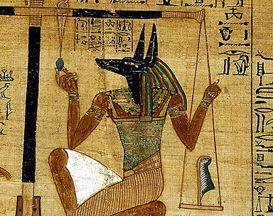 Anubis, weighing a heart against a feather in the Egyptian Book of the Dead.