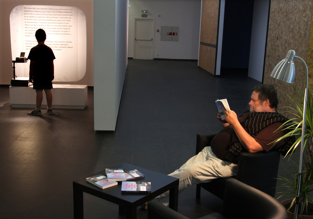 Figure 2. Installation view of Contarlo todo sin saber cómo at CA2M with copies of Manen's novel in the foreground. The beginning of the novel was projected in the gallery, which is visible in the upper left corner of this image. Credit: Jaime Villanueva (Creative Commons)