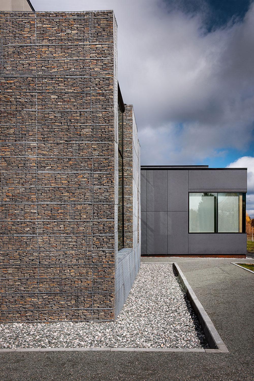 Vue des murs en gabion contrastant avec les panneaux de fibre de béton