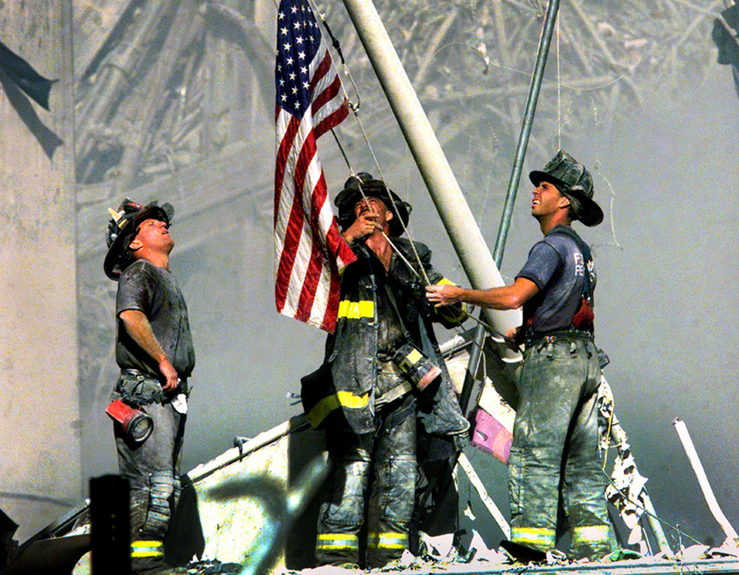 [Firefighters raising the American flag after the 9/11 attacks]
