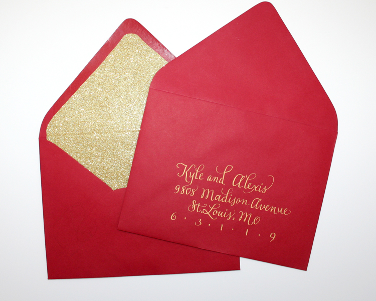 Bright red paper source envelopes, gold glitter liners, finished with custom hand lettered gold metallic addresses