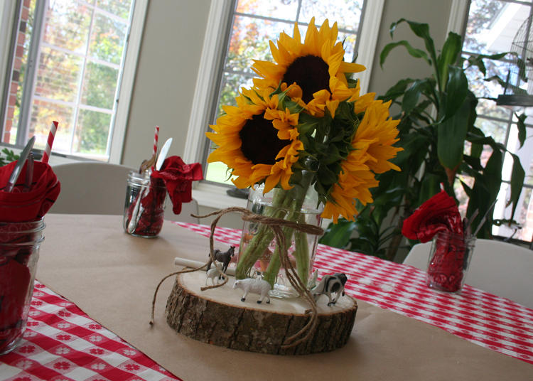 The centerpieces were so simple, yet cute as can be! A cut log with little farm animals and a jar of sunflowers were placed on each table.