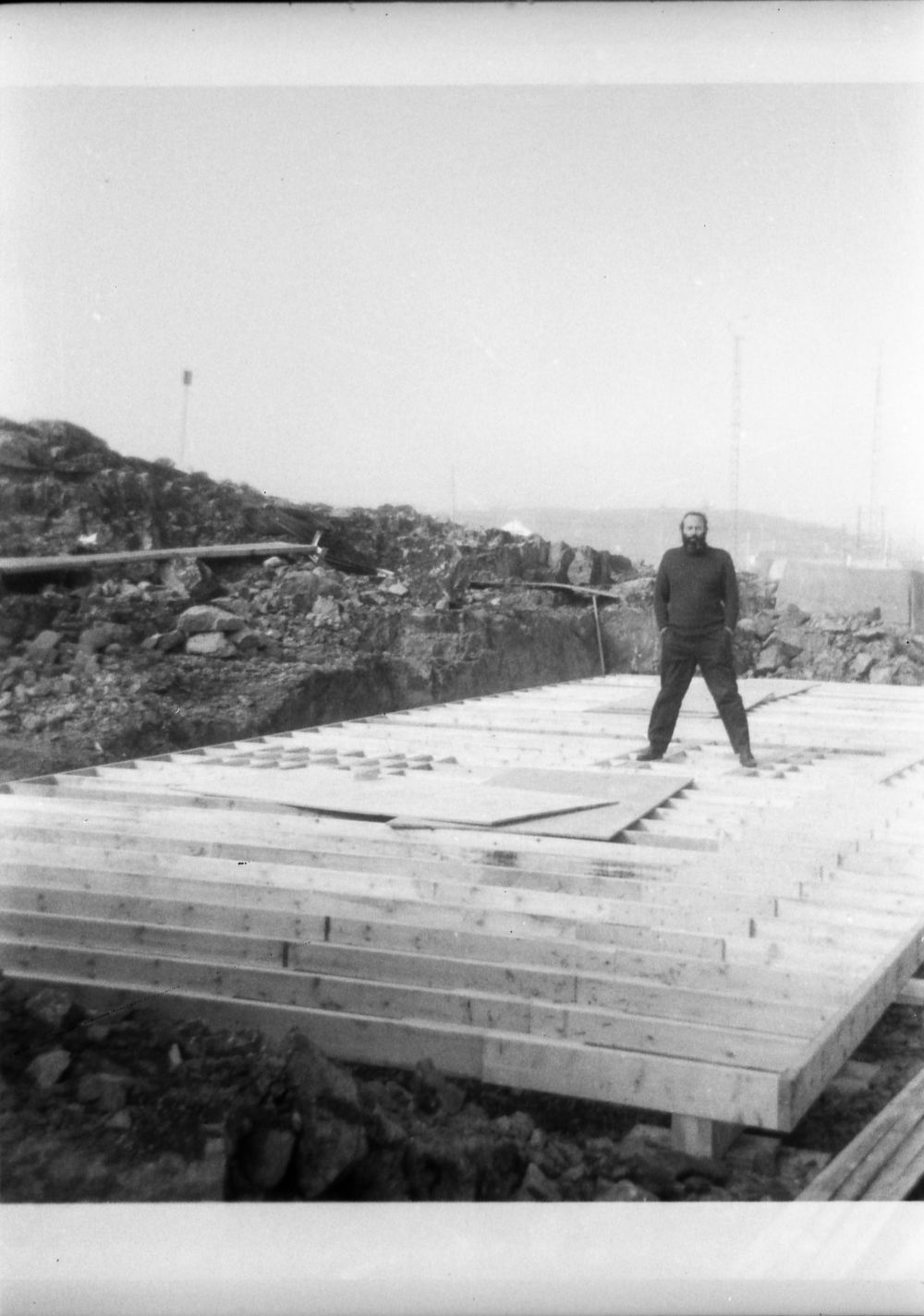 "A previously unseen photo showing Wil on the new floor of the typography building. I had always understood that there was a cement pad poured where the press was going to be put but clearly you can see that it was just reinforced in two places. Wil is standing on the location of  the ""Little Giant"" press. The other spot, to the left of Wil, is where either the Vandercook 4T or the platen press eventually sat.  Photo: HH Johnston Collection, courtesy Sean Johnston."