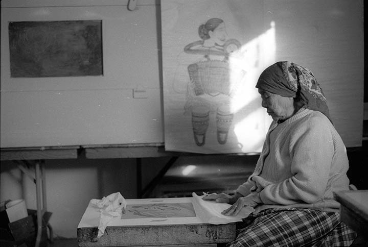 "Atami Regge drawing on a litho stone. Note in the background is the aquatint box and to the right behind the drawing by Napachie of her accordian lady is the old acid bath compartment. This photo is a scan of a black and white negative I took ""back in the day""."