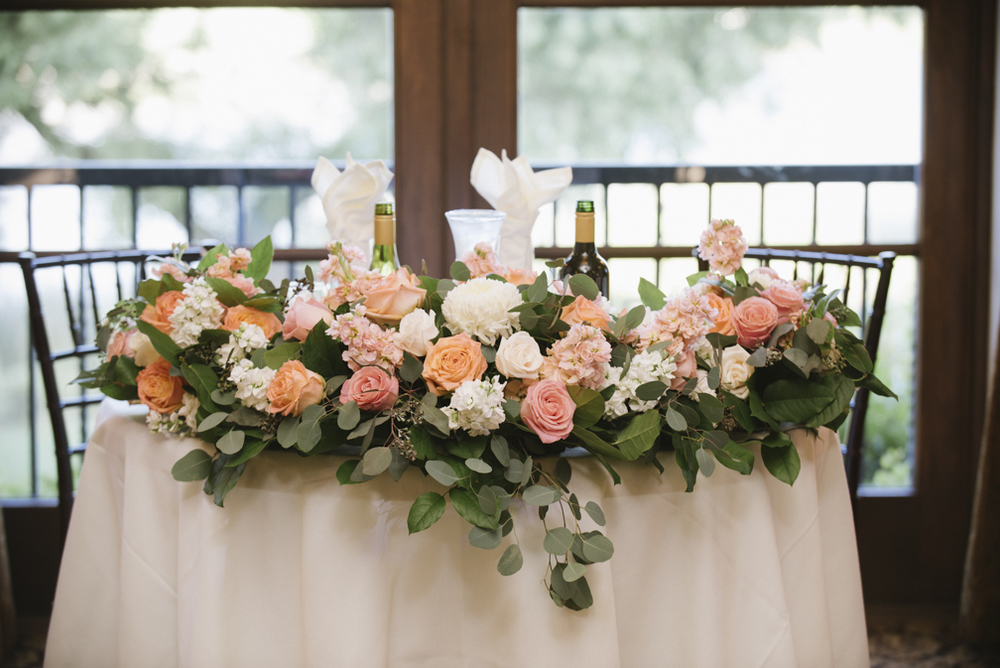 salmon and white wedding sweetheart table floral