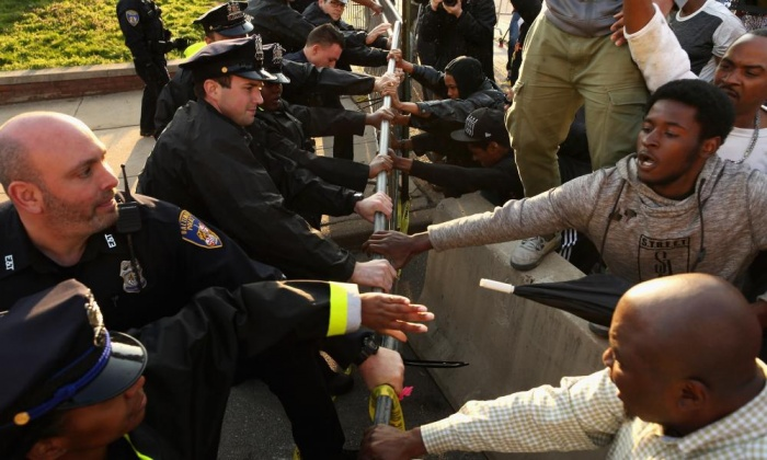 Demonstrators and police officers wrestle over a metal barricade during the protest on Wednesday in West Baltimore. Photograph: Chip Somodevilla/Getty Images