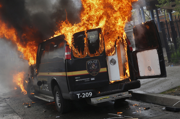 A Baltimore Metropolitan Police transport vehicle burns during clashes in Baltimore, Maryland April 27, 2015. (Credit: Reuters/Shannon Stapleton)
