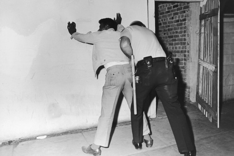 A police officer searches a suspect during the Watts Rebellion. Express / Archive Photos / Getty Images