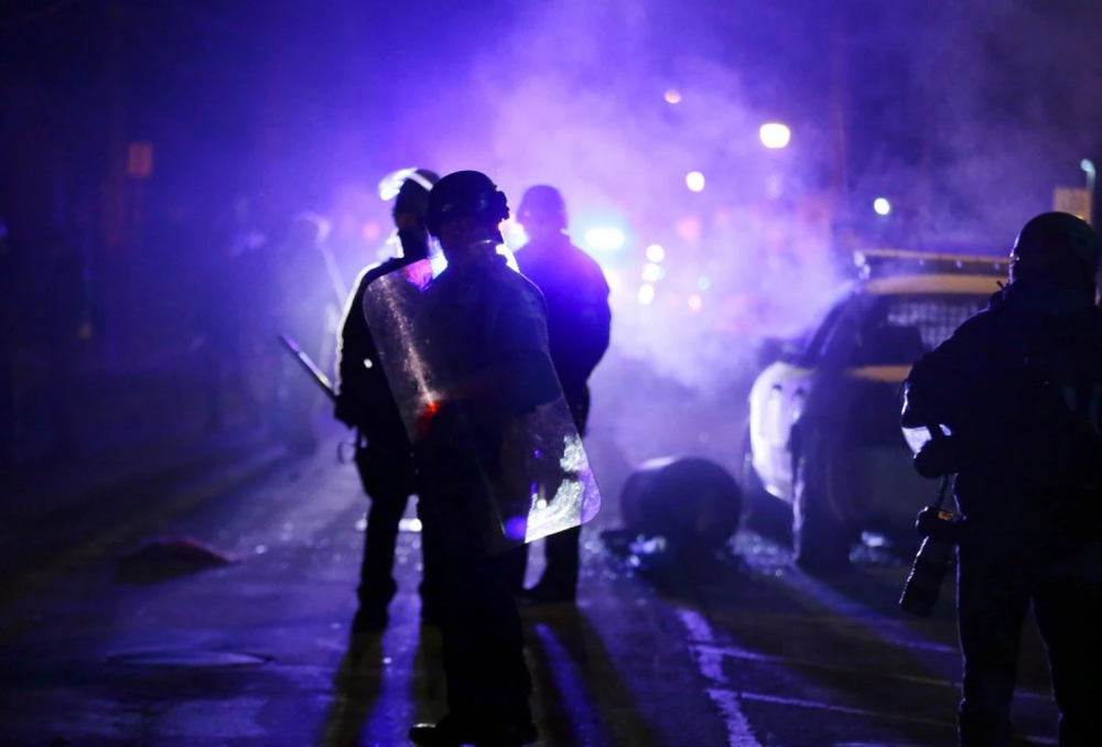 Police officers watch protesters as smoke fills the streets in Ferguson, Mo., in November after a grand jury's decision in the fatal shooting of Michael Brown. (Charlie Riedel/AP)