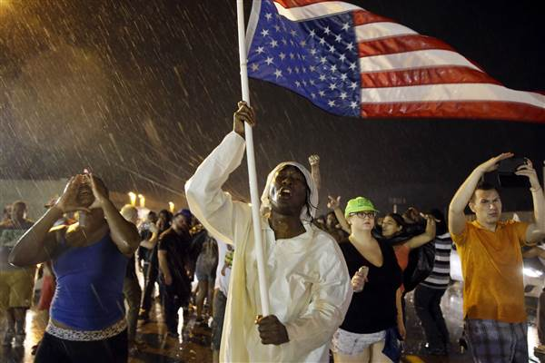 Protesters march in the rain, Sunday, Aug. 9, 2015, in Ferguson, Mo. S     Jeff Roberson / AP