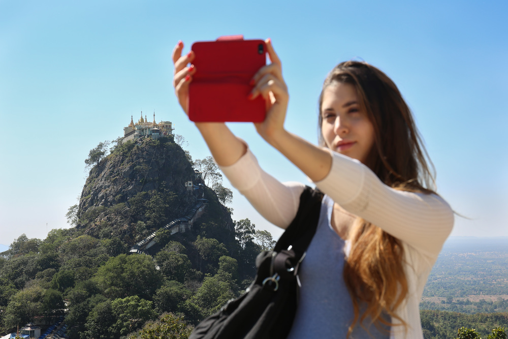 A young tourist takes a selfie in front of the sacred Mount Popa, on top of which sits a popular pilgrimage destination for the Burmese.
