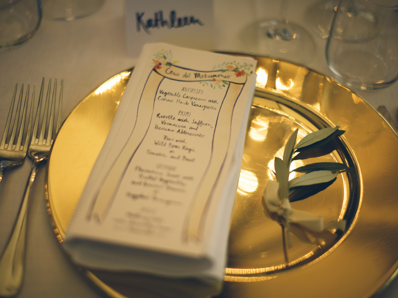 Above: a close up of the dinner menu framed by shiny gold chargers at each guest's seat. Image by  Lelia Scarfiotti.