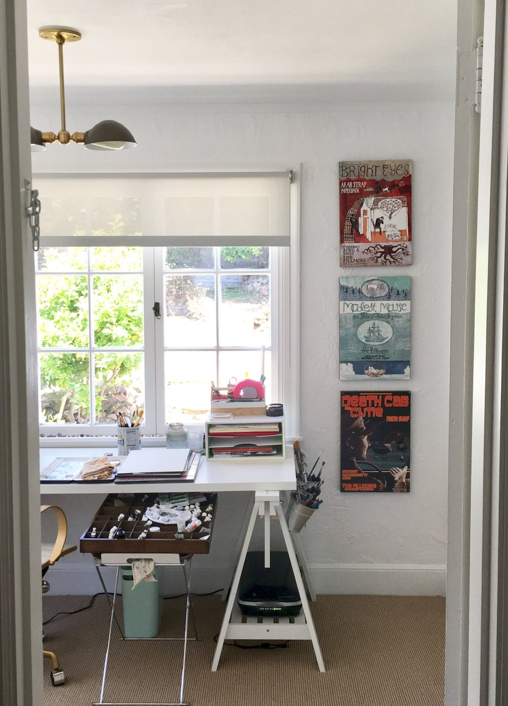 Looking in from the hallway we made when we separated this sun room from the bedroom. I use a lot of hot pink artist's tape. And I use a vintage letterpress tray to keep my paints (semi) organized. We collected the posters from concerts at the Fillmore over the years.