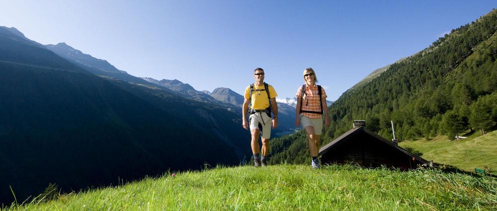 Wanderer vor Alm auf grüner Wiese.jpg
