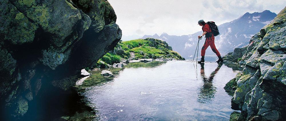 Wanderin überquert ruhigen Bachlauf.jpg