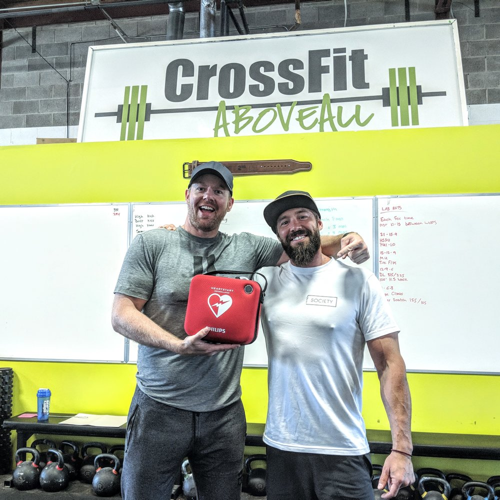 July 2018: Instructor Jarrett Chisholm with CrossFit Above All owner Curtis Laughren showing off the AED purchased with funds raised from the November 2017 First Aid fundraiser.