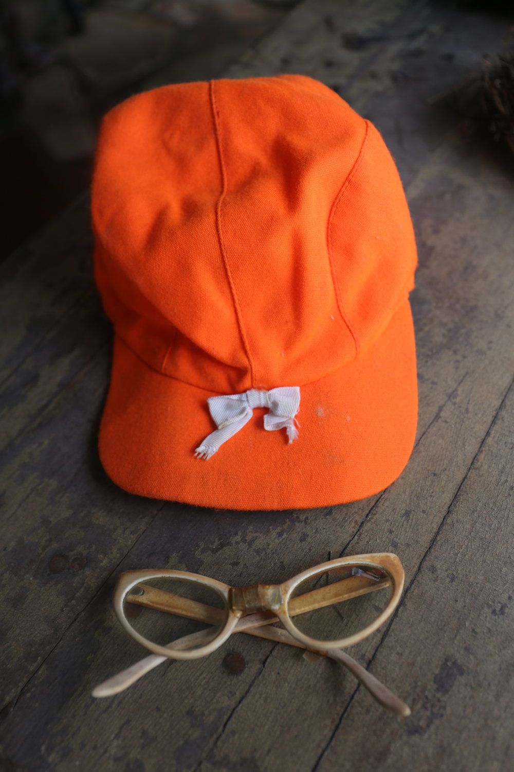 Kay's hunting cap and iconic cat eye glasses.