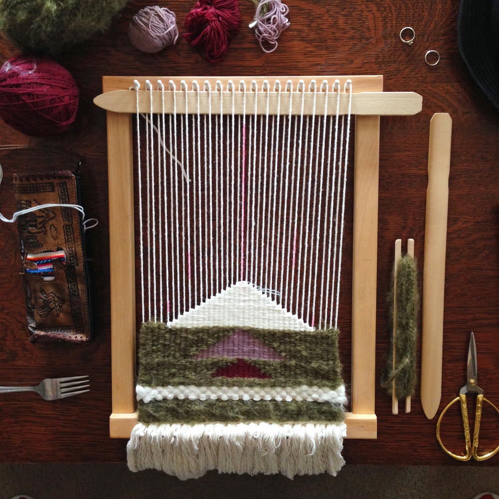 Nearing the half-way point. I've been using a fork as a weaving comb to pack down my yarns as I weave.