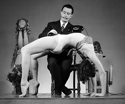 Dali with unnamed woman in Urdva Danurasana/Chakrasana in an unknown place/year. Look at the left side of the photo. I think there is someone in shoulderstand or headstand partially submerged in a plant? Yes please!