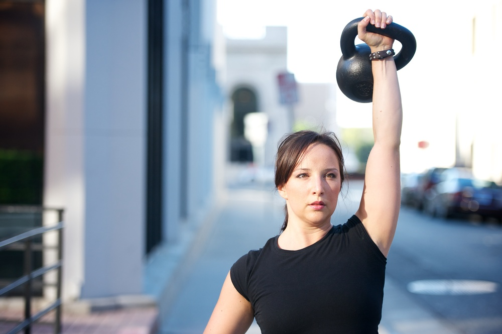 Photo of Anne standing on a city street, doing a kettlebell snatch.