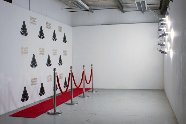 "Proposal for a televised awards ceremony (installation view), 2018  ""Proposal for a televised awards ceremony"" allows viewers to walk on the red carpet for a fictional contemporary art themed awards ceremony. Simulating an onslaught of camera flashes, strobe lights intermittently illuminate the space, their nauseating presence accompanied by an audio track that combines newly recorded and found audio about the pros and cons of competitions."