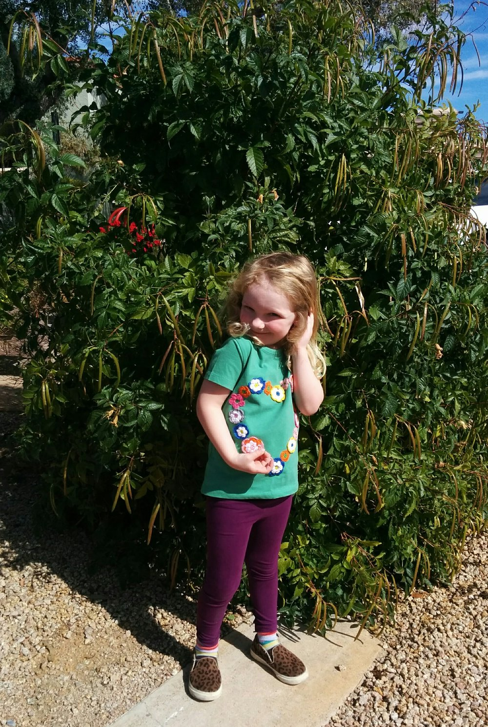 Posing in front of a plant. She loves pictures right now!