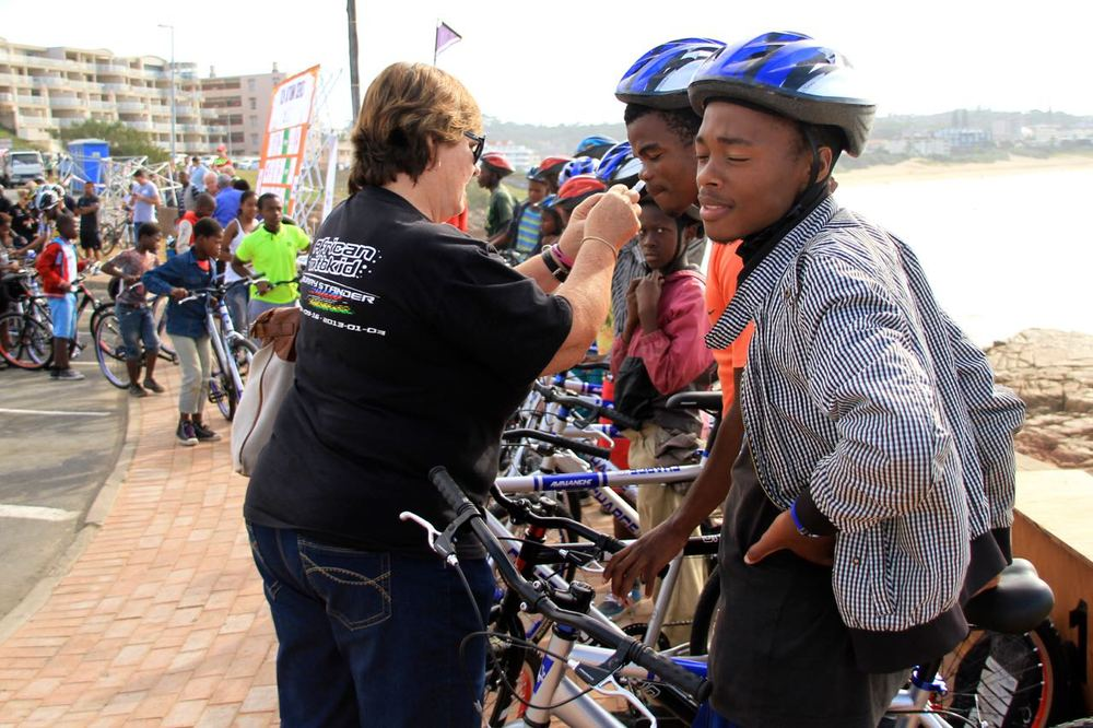 The Burry Stander Foundation's Mandie Stander assists her young riders in fitting their brand new helmets that they received with their brand new bicycles as part of the Hibiscus Coast Cycling Festival in Margate today. Photo: supplied