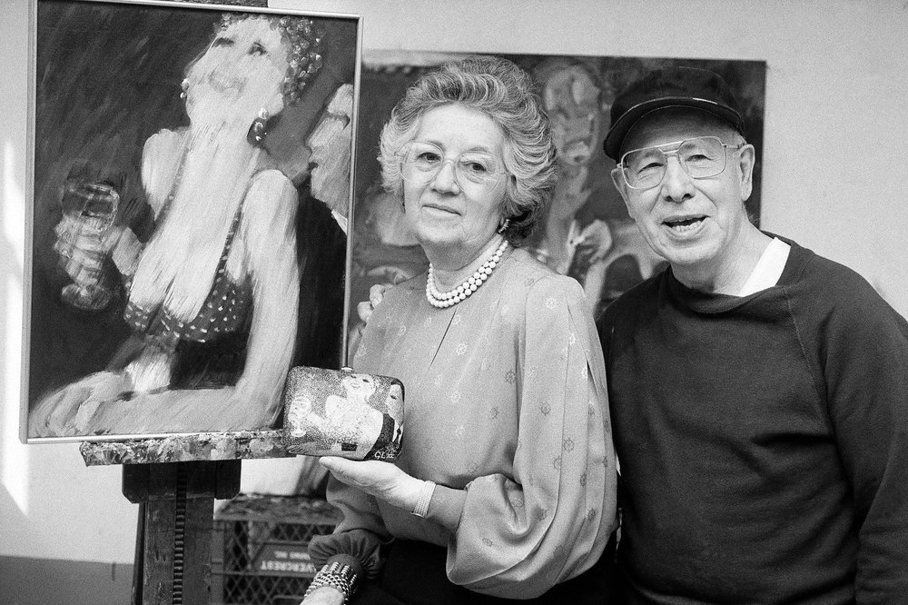 The Leibers posing with a handbag designed after one of Gus's paintings; image: The New York Times.