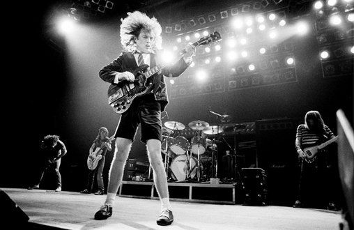 AC/DC  lead guitarist Angus Young performs in signature schoolboy uniform; image via Pinterest.