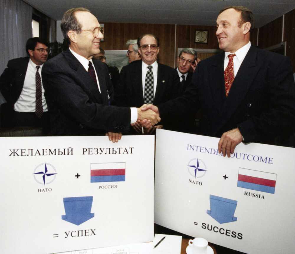"""Russia + NATO = Success."" Perry and Russian defense minister Grachev sign Bosnia agreement at NATO headquarters in Brussels, November 1995."