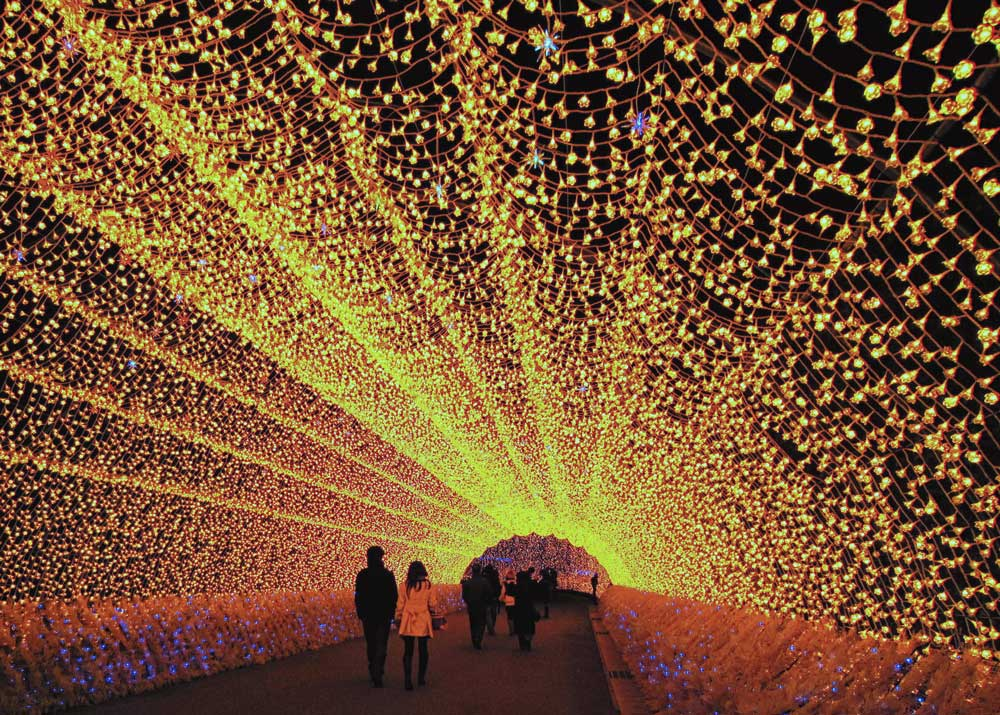 A couple walks through the light tunnel in Nabana no Sato.