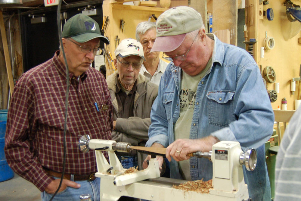 Bill Weist, Litton Frank, and Rick Baker look on as Ed works on a spatula.