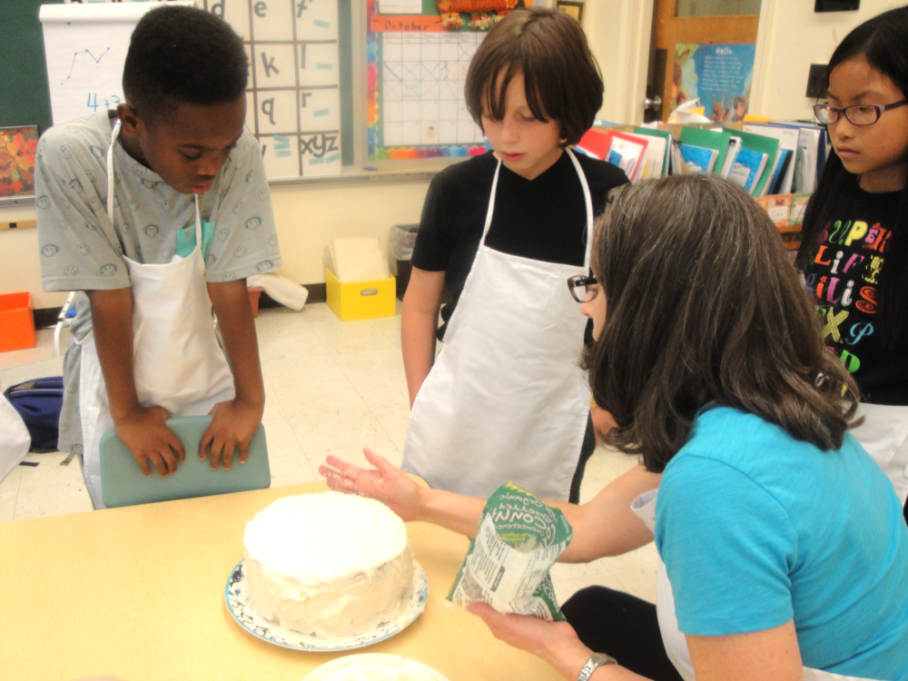 Ms. Lynley demonstrates pressing the shredded coconut into the sides of the cake so the children can take turns doing it.