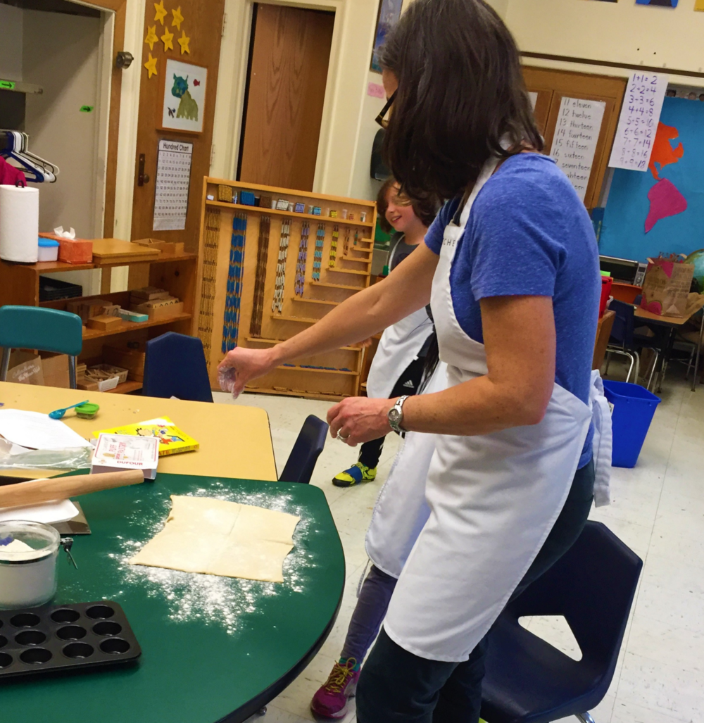 Ms. Lynley is preparing the puff pastry to be rolled and cut by the children