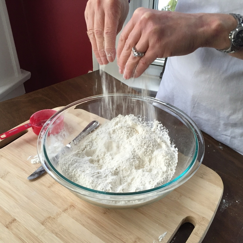 Using fingers to cut butter into pie crust pastry