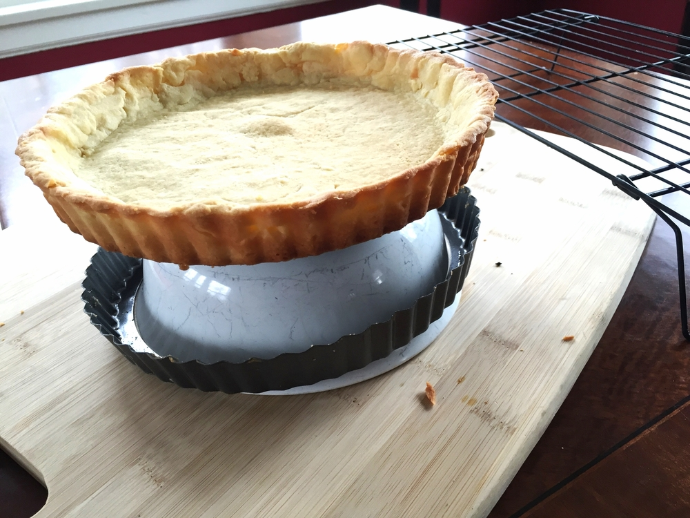 Removing outer ring of hot tart shell over a bowl.