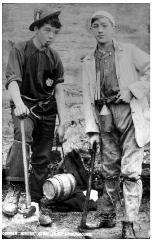 Boys working in the mines. Note the small wooden barrel lunchbox held by the boy on the left - likely containing a Cornish Pasty. Both boys have candles, which were used before electric lights to help the miners see underground. The boy on the left has attached a candle to his hat with a glob of clay, which was typical at the time.   Source:  Greever Tin Mine Museum website.
