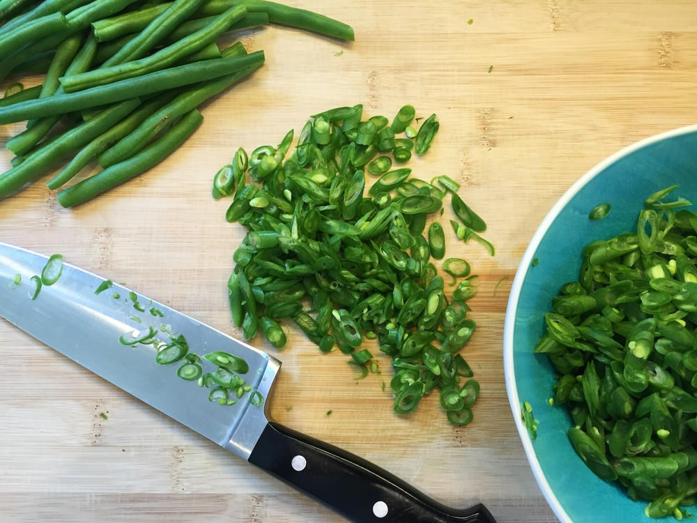 Slicing the green beans into small diagonal pieces.