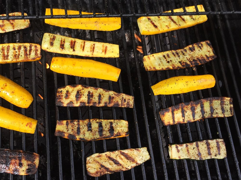 Green and yellow zucchini on the Adventure Kitchen grill.