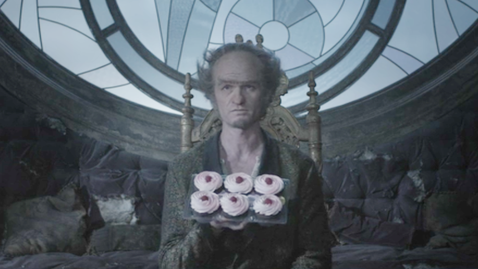 This image, obtained from the Netflix corporation by one of my associates, shows Count Olaf holding a tray of ersatz raspberry cupcakes in his filthy dining room.