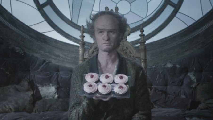 Obtained by one of my associates, this still image from the Netflix corporation shows Count Olaf proffering his ersatz raspberry cupcakes.