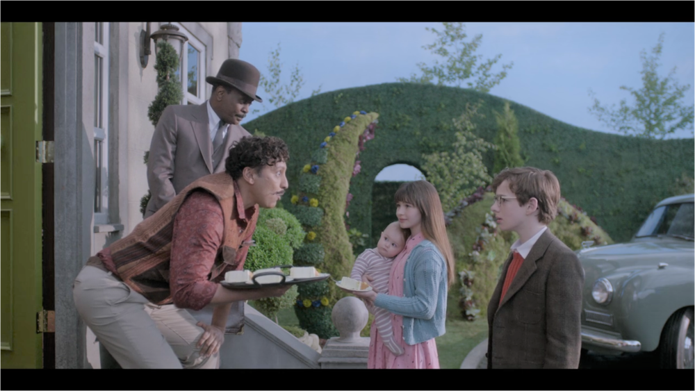 This still image, obtained under perilous circumstances from the Netflix corporation, shows Dr. Montgomery Montgomery offering coconut cream cake to the Baudelaires, as Mr. Poe stands nearby fabricating an excuse to decline eating a slice.