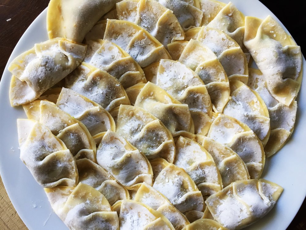 A plate of potstickers waiting to be cooked