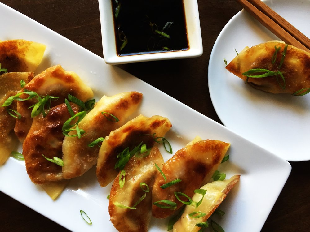 A plate of potstickers, with a potsticker on another plate nearby, and dipping sauce