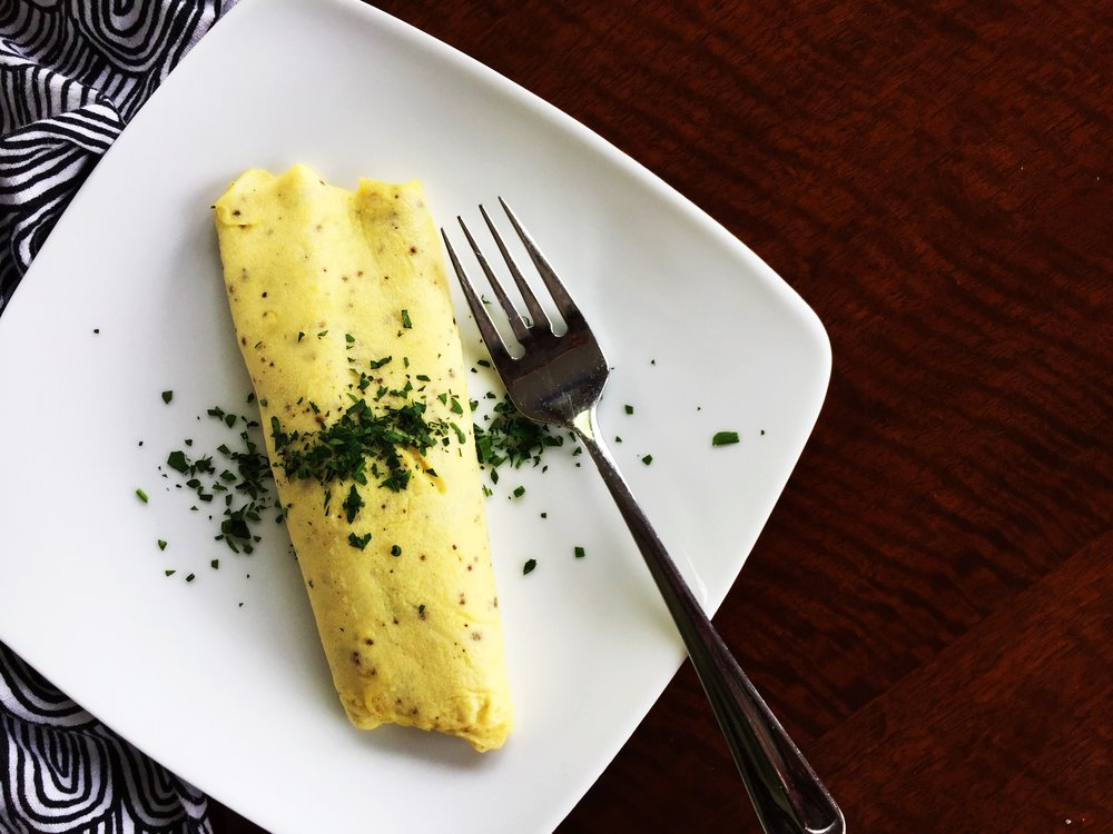 A delicious omelette sprinkled with herbs, awaiting the first bite