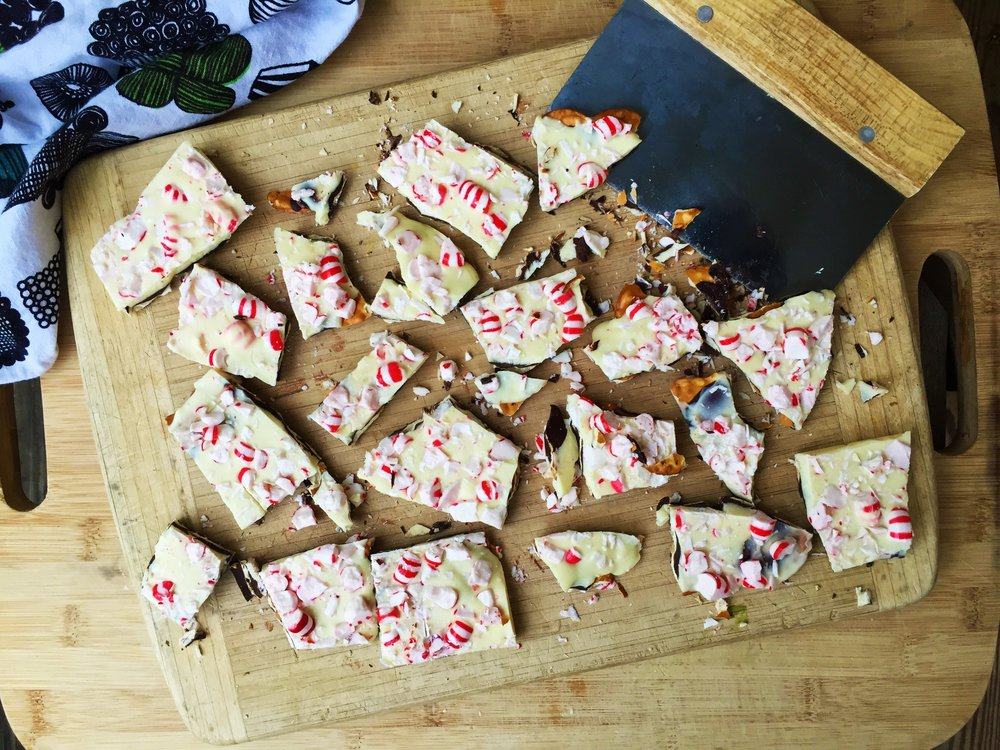 Peppermint Pretzel Bark broken into pieces on a cutting board