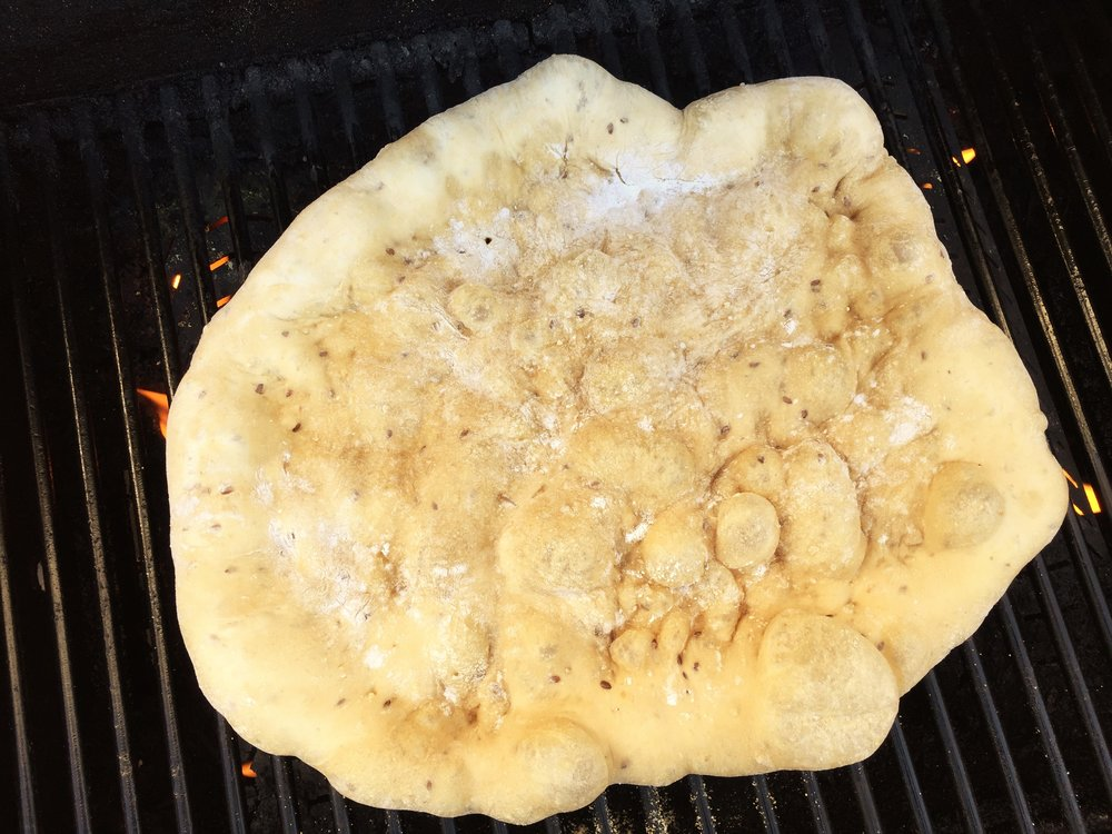 Multigrain pizza dough on the Adventure Kitchen grill, prior to flipping